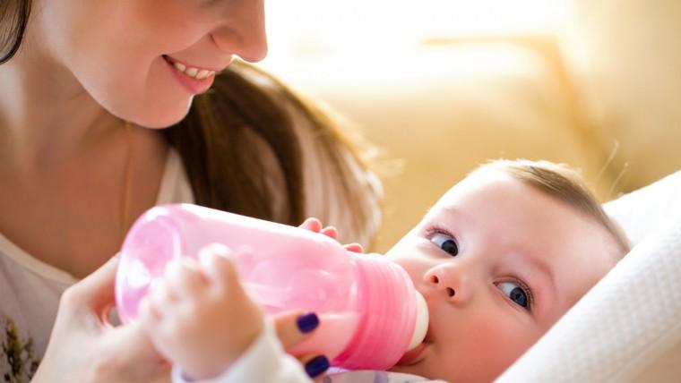 bébé buvant le biberon avec sa maman